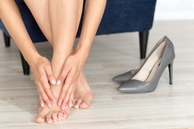 Vermoeide en pijnlijke vrouwelijke voeten na het lopen