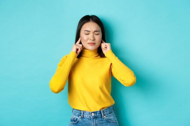 Vermoeide en teleurgestelde jonge aziatische vrouw die niet wil luisteren, oren sluit met vingers en ogen dicht, staande in ontkenning over blauwe achtergrond