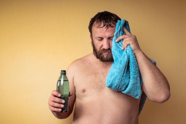 Vermoeide en uitgeputte halfnaakte bebaarde man houdt een fles water vast en veegt het zweet van het voorhoofd