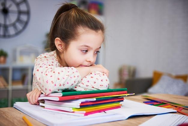 Vermoeide en verveelde student met stapel boeken