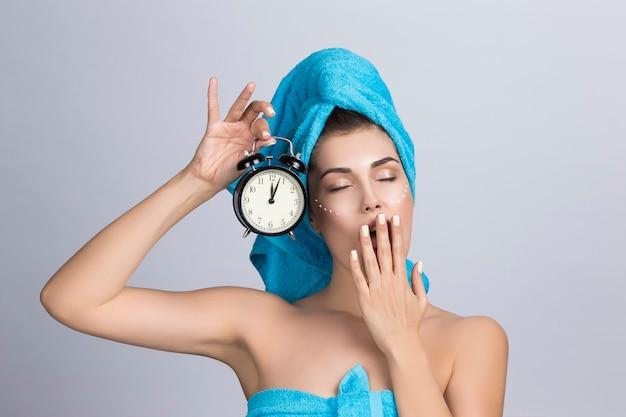 Vermoeide gapende vrouw in handdoek op hoofd en crème op gezicht met wekker met middernacht, nachtcrème huidverzorgingsconcept