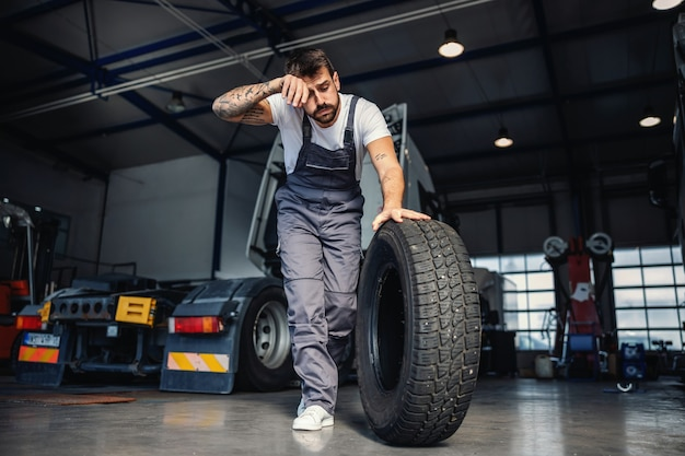 Vermoeide hardwerkende mechanische rolband om deze op de vrachtwagen te vervangen. hij staat in garage van import- en exportbedrijf.