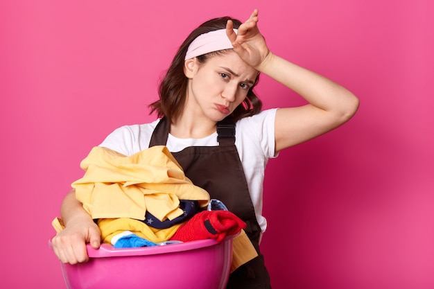 Vermoeide, hardwerkende vrouw met fronsend gezicht die haar voorhoofd met de hand aanraakt, zweet wegveegt, veel huishoudelijk werk heeft, schone kleren uit de was haalt, verdrietig kijkt.