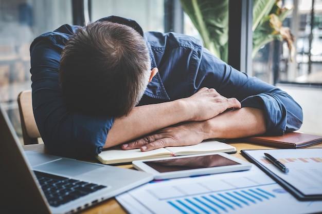 Vermoeide hogere zakenmanslaap die lange werkdag hebben die op lijst in zijn bureau wordt overwerkt