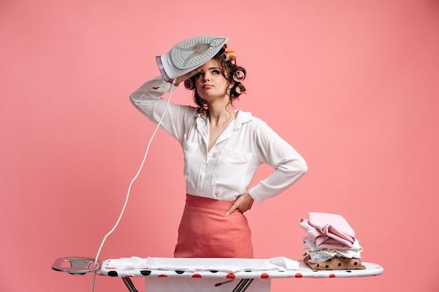 Vermoeide huisvrouw die kleren op strijkplank strijken
