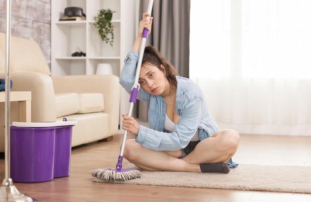 Vermoeide huisvrouw na het schoonmaken van de vloer van het appartement
