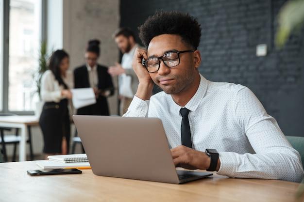 Vermoeide jonge afrikaanse zakenman die laptop computer met behulp van