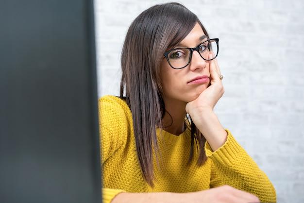 Vermoeide jonge bedrijfsvrouw bij bureau
