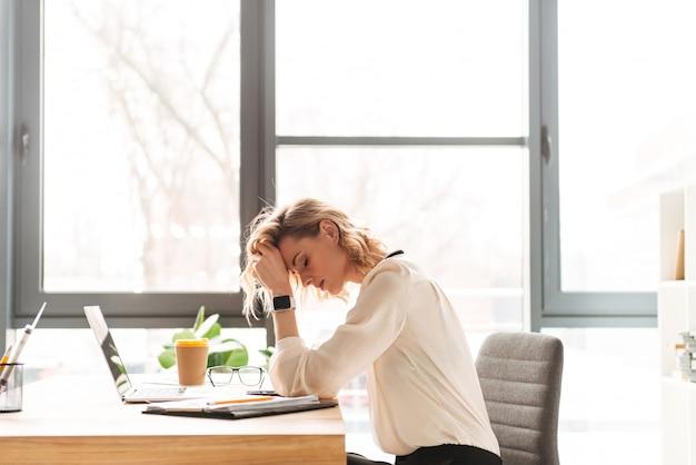 Vermoeide jonge bedrijfsvrouwenzitting in bureau dat laptop met behulp van