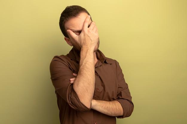 Vermoeide jonge blanke man die gezicht bedekt met hand met gesloten ogen geïsoleerd op olijfgroene achtergrond met kopie ruimte