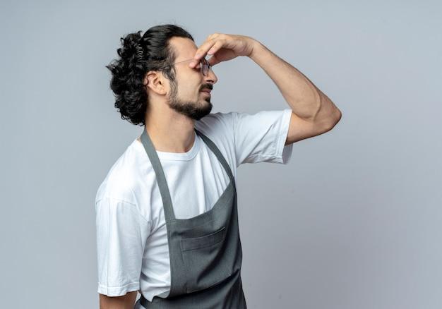 Vermoeide jonge blanke mannelijke kapper bril en golvende haarband dragen uniform vingers zetten ogen geïsoleerd op een witte achtergrond met kopie ruimte