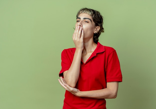 Vermoeide jonge blanke meisje met pixie kapsel kijken kant geeuwen met handen op de mond en onder de elleboog geïsoleerd op olijfgroene achtergrond met kopie ruimte