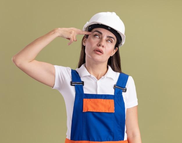 Vermoeide jonge bouwersvrouw in uniform die zelfmoord met pistoolgebaar toont dat op olijfgroene muur wordt geïsoleerd