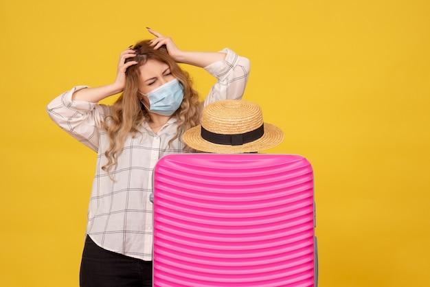Vermoeide jonge dame die masker draagt dat kaartje toont en zich achter haar roze zak bevindt