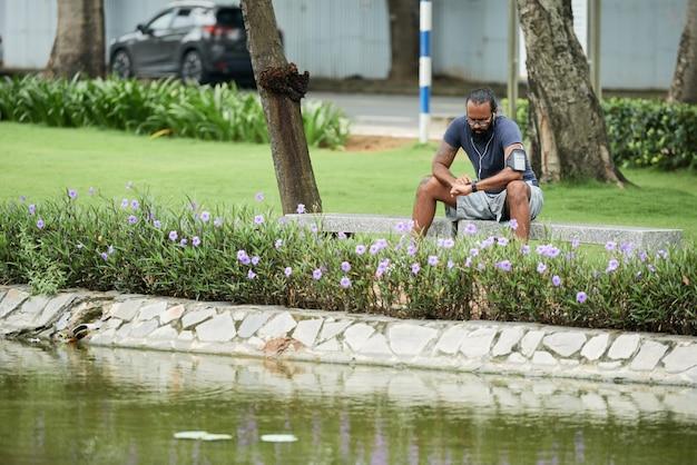 Vermoeide jonge indiase atleet in oortelefoons zittend op een bankje in het stadspark en polsslag controleren na de training