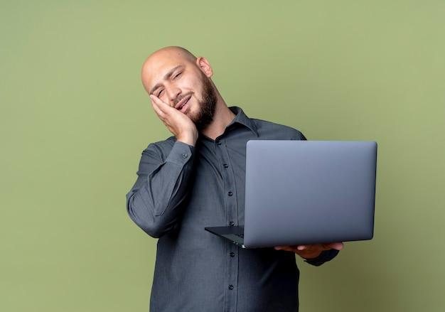 Vermoeide jonge kale callcentermens met laptop die hand op gezicht zet dat op olijfgroene muur wordt geïsoleerd