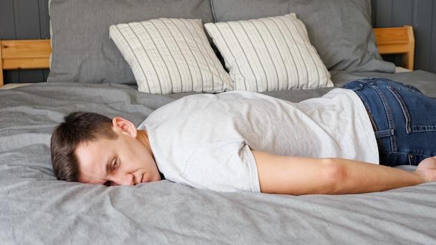 Vermoeide jonge kerel in t-shirt ligt op een groot bed met grijs linnen en designer kussens in een moderne kamer thuis close-up