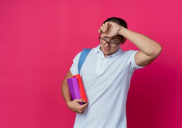 Vermoeide jonge knappe mannelijke student die achterzak en glazen draagt die boeken houdt