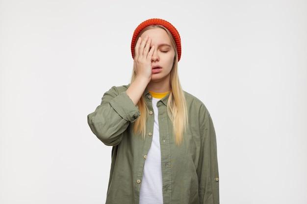 Vermoeide jonge knappe withoofdige dame die haar ogen sluit en kegelvormig gezicht met opgeheven handpalm terwijl poseren op blauw in rode hoed, olijfgroen overhemd en wit t-shirt