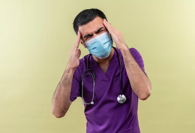 Vermoeide jonge mannelijke arts die paarse chirurgenkleding en een stethoscoop medisch masker draagt, legt zijn handen op het voorhoofd op geïsoleerde groene muur