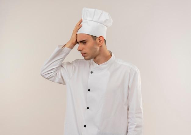 Vermoeide jonge mannelijke kok die eenvormige chef-kok draagt die hand op hoofd met exemplaarruimte zet