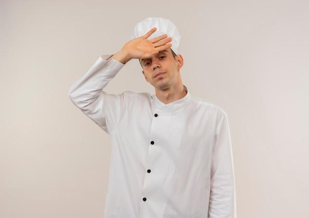 Vermoeide jonge mannelijke kok die eenvormige chef-kok draagt die hand op voorhoofd met exemplaarruimte zet