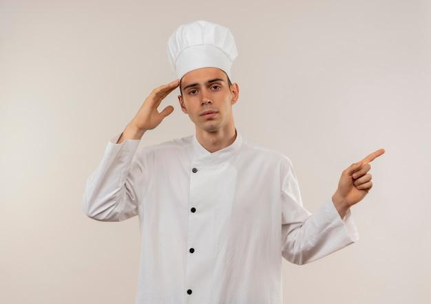 Vermoeide jonge mannelijke kok die eenvormige chef-kok draagt die hand op voorhoofd zet wijst vinger aan kant met exemplaarruimte