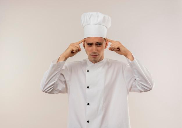 Vermoeide jonge mannelijke kok die eenvormige chef-kok draagt die vingers op zijn voorhoofd met exemplaarruimte zet