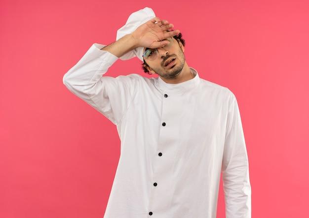 Vermoeide jonge mannelijke kok die uniforme chef-kok en glazen draagt die hand op voorhoofd zetten