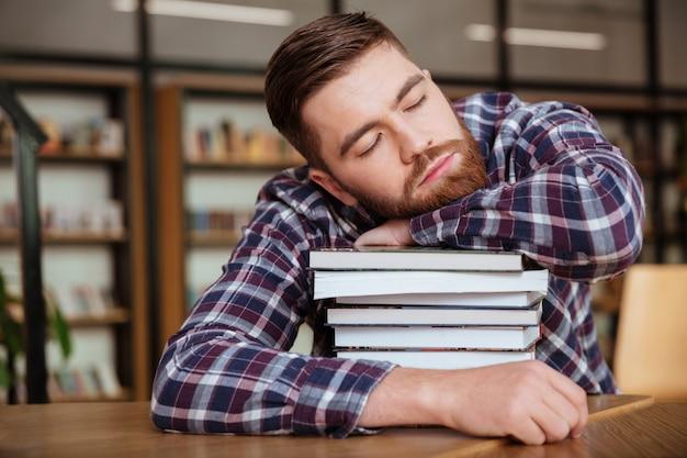 Vermoeide jonge mens die zijn hoofd op de boekstapel houdt