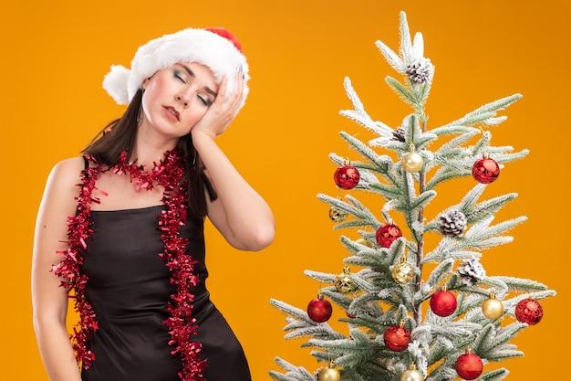 Vermoeide jonge mooie blanke meisje met kerstmuts en klatergoud slinger om nek staande in de buurt van versierde kerstboom op oranje achtergrond