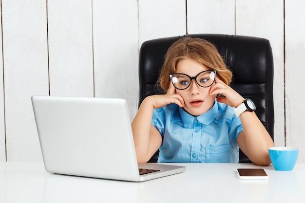Vermoeide jonge mooie meisjeszitting op werkende plaats in bureau.