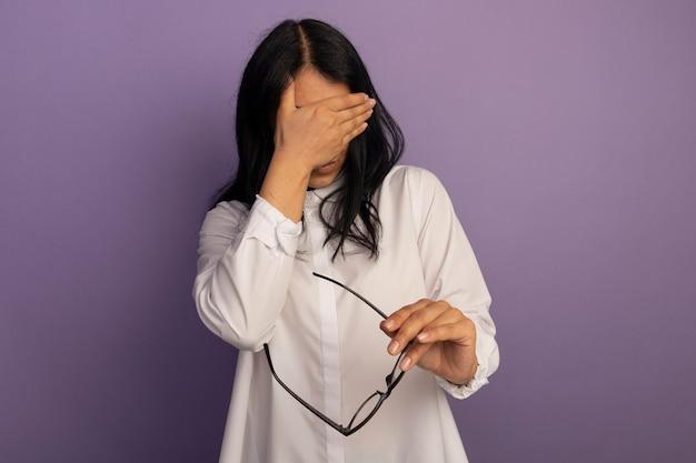 Vermoeide jonge mooie vrouw, gekleed in een wit t-shirt met een bril bedekt gezicht met de hand