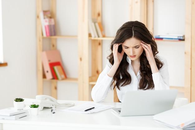 Vermoeide jonge onderneemster die aan lange tijd achter computerbureau in bureau lijdt.