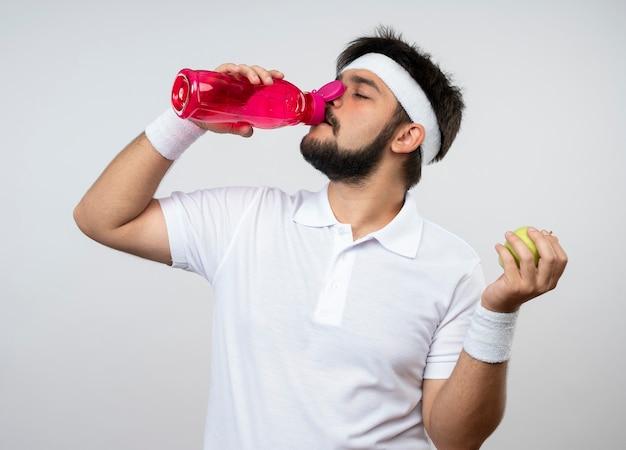 Vermoeide jonge sportieve man met hoofdband en polsband drinkt water met appel geïsoleerd op een witte muur