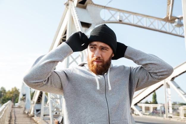 Vermoeide jonge sportman met hoed die zich klaarmaakt om te joggen terwijl hij op de brug staat