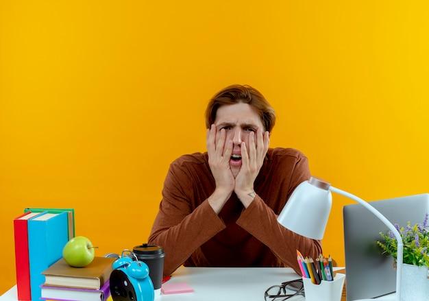 Vermoeide jonge studentenjongen zit aan bureau met schoolgereedschap bedekt gezicht met handen op geel