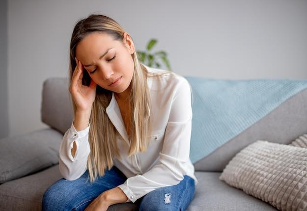 Vermoeide jonge vrouw die aan hoofdpijn lijdt