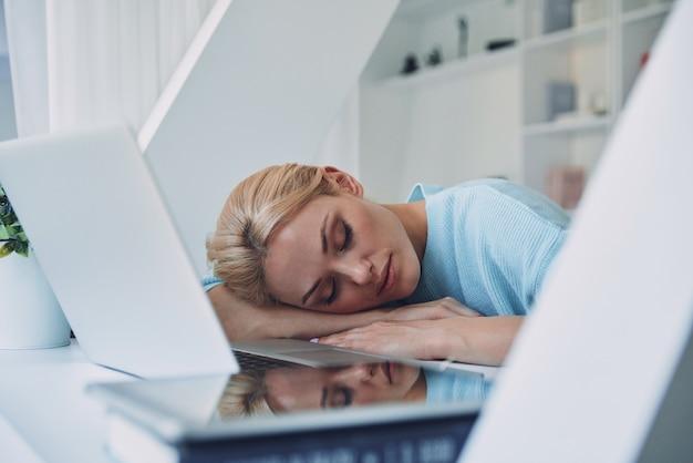 Vermoeide jonge vrouw die slaapt terwijl ze op haar werkplek op kantoor zit