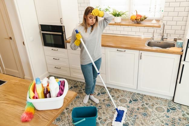 Vermoeide jonge vrouw huisvrouw in handschoenen rusten tijdens het dweilen van de vloer in de moderne keuken