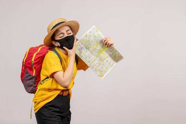 Vermoeide jonge vrouw met rode rugzak die kaart op grijs houdt