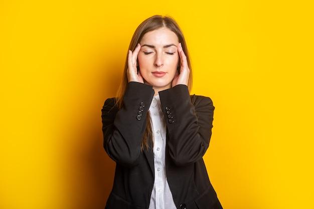 Vermoeide jonge vrouw van het werk met gesloten ogen, die haar handpalmen op haar slaap op een geel vasthoudt.