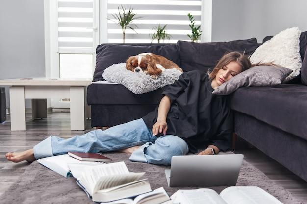 Vermoeide jonge vrouw viel thuis in slaap terwijl ze op laptop werkte