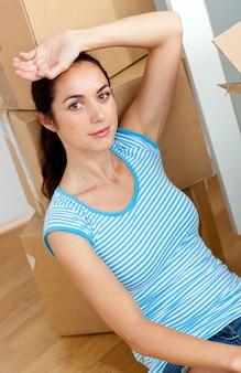 Vermoeide jonge vrouw zittend op de vloer na het uitpakken van karton