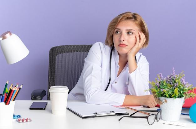 Vermoeide jonge vrouwelijke arts die een medisch gewaad met een stethoscoop draagt, zit aan tafel met medische hulpmiddelen geïsoleerd op blauwe achtergrond