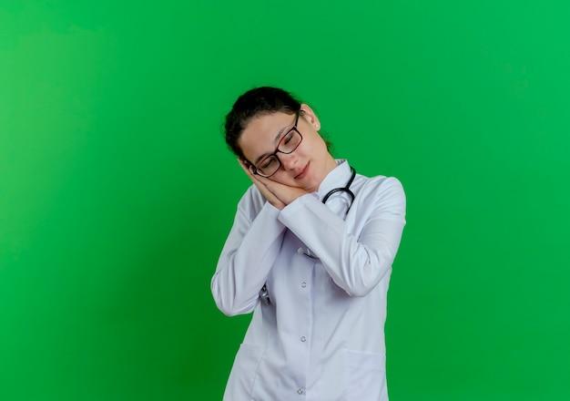 Vermoeide jonge vrouwelijke arts die medisch kleed en een stethoscoop en een bril draagt die slaapgebaar met gesloten ogen doet die op groene muur met exemplaarruimte wordt geïsoleerd