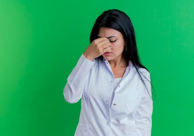 Vermoeide jonge vrouwelijke arts die medische gewaad draagt die neus met gesloten ogen houdt die op groene muur met exemplaarruimte wordt geïsoleerd