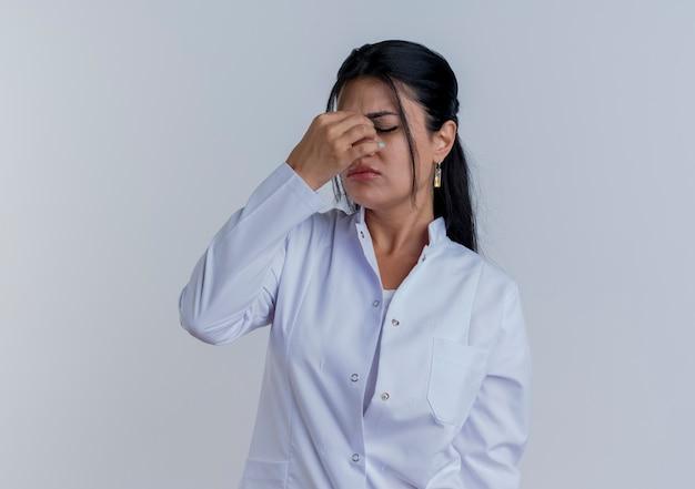 Vermoeide jonge vrouwelijke arts die medische gewaad draagt die neus met gesloten ogen houdt die op witte muur met exemplaarruimte wordt geïsoleerd