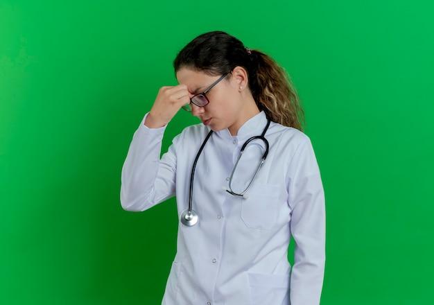 Vermoeide jonge vrouwelijke arts die medische robe en stethoscoop en glazen draagt die neus met gesloten ogen houdt die op groene muur met exemplaarruimte wordt geïsoleerd