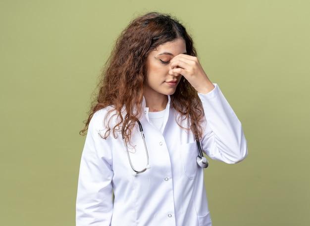 Vermoeide jonge vrouwelijke arts met een medisch gewaad en een stethoscoop die neus vasthoudt met gesloten ogen geïsoleerd op olijfgroene muur